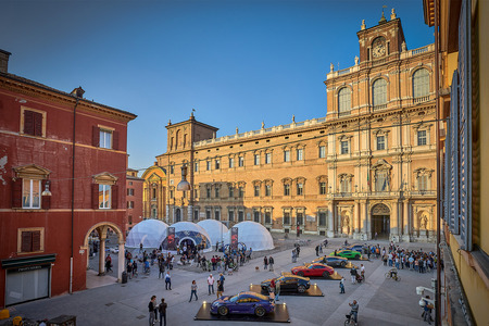 The Piazza Roma in Modena, with domes containing the racing sleds and a display of real cars included in Gran Turismo Sport. The building is the Palazzo Ducale.
